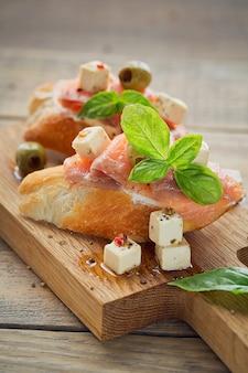 Bruschetta with smoked salmon, cream cheese, olives and arugula
