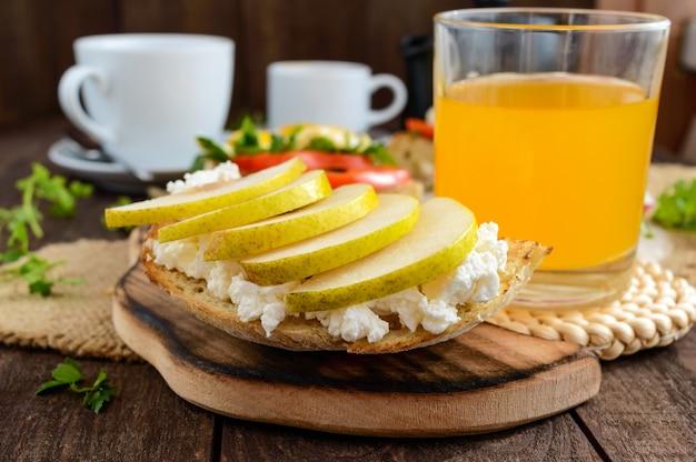 柔らかいチーズ、ジューシーな洋ナシ、フレッシュジュースのグラスとブルスケッタ。エコ朝食。フィットネスメニュー