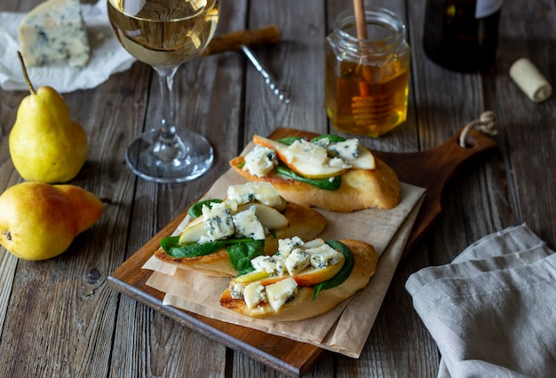 Bruschetta with spinach, pear and blue cheese. wine. vegetarian food. healthy eating. veganism. diet.