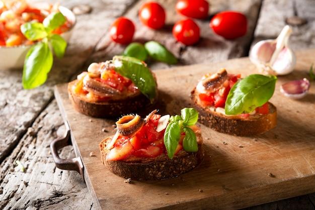 木の板にトマト、バジルのアンチョビ、オリーブオイルを添えたブルスケッタ。伝統的なイタリアの前菜またはスナック、前菜