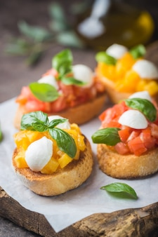 Bruschetta with tomato, basil and mozzarella cheese on wooden board