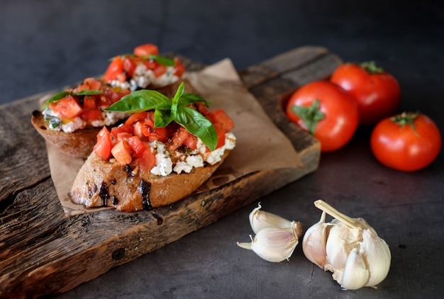 Bruschetta with tomato, basil and village cheese on wooden board with tomatoes table. traditional italian appetizer or snack