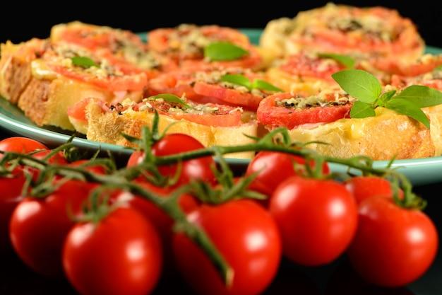 Bruschetta with tomato, parmesan, olive oil, ham and oregano