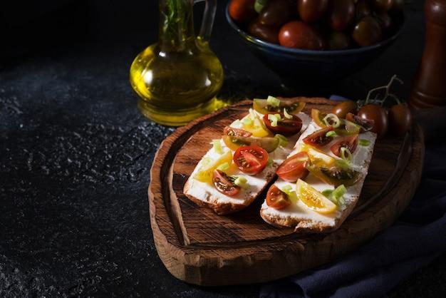 木の板にトマトとオリーブオイルを添えたブルスケッタ-伝統的なイタリア料理、スペイン料理の軽食、厳選されたフォーカス