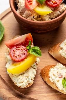 Брускетта с помидорами, сливочным сыром и базиликом. вкусный завтрак или закуска, чистое питание, диета, концепция веганского питания. вид сверху.