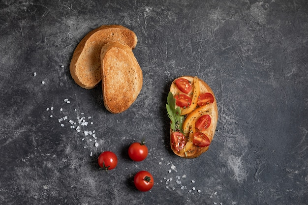 Bruschetta with tomatoes in the hands on a dark background, top view.