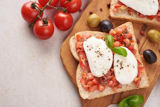 도마에 토마토, 모짜렐라 치즈, 바질과 브루스케타. 전통적인 이탈리아 전채 또는 간식, 전채 요리. 카프레제 샐러드 브루스케타. 복사 공간이있는 상위 뷰. 평평하다.