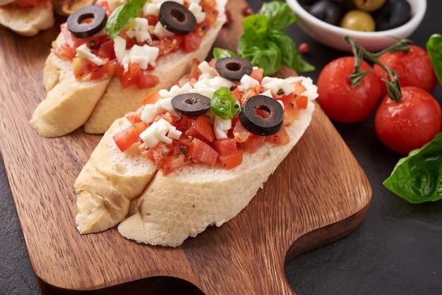 まな板にトマト、モッツァレラチーズ、バジルを添えたブルスケッタ。伝統的なイタリアの前菜またはスナック、前菜。カプレーゼサラダのブルスケッタ。コピースペースのある上面図。フラットレイ。