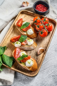 Bruschetta with tomatoes, mozzarella cheese and basil. italian appetizer or snack, antipasto