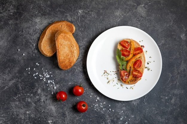 Bruschetta with tomatoes on a white plate against dark background, top view