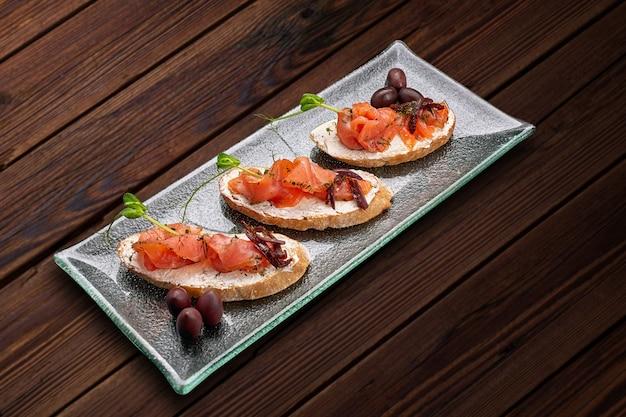 Брускетта с форелью, лососем, сливочным сыром и микрозеленью на стеклянной тарелке на деревянном столе