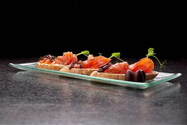 Брускетта с форелью, лососем, сливочным сыром и микрозеленью на стеклянной тарелке