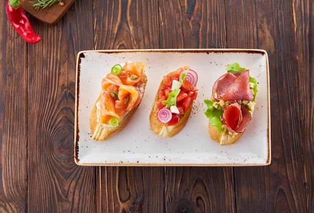 Bruschetta with various toppings, variety of small sandwiches with salmon red fish, fresh vegetables, tomatoes and herbs on wooden table