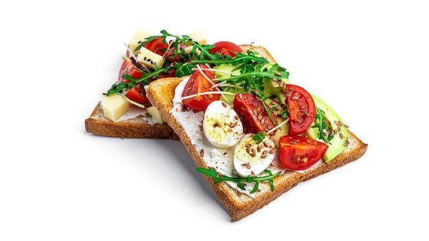 Брускетта с овощами, перепелиными яйцами и сыром на белом фоне. фото высокого качества
