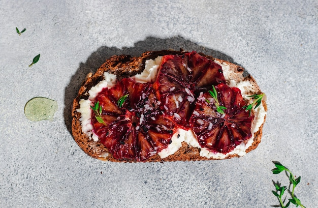 Bruschetta with whole grain bread, cottage cheese, blood orange, thyme