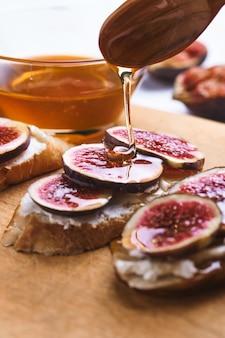 Брускетты с инжиром, мягким сыром и медом на деревянной доске.