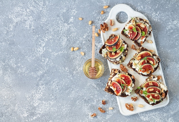 Bruschettas with fresh figs, ricotta, nuts and honey on light table, flat lay