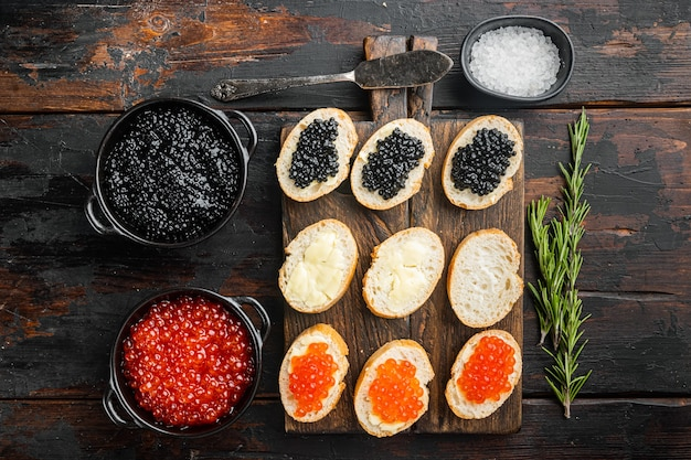 Bruschettes with butter red, and black caviar, on old dark  wooden table table, top view flat lay