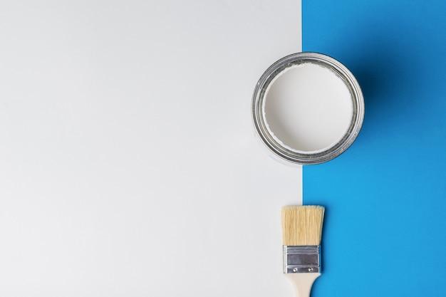 Кисть и банка с открытой белой краской на сине-белом фоне. выполнение малярных работ.