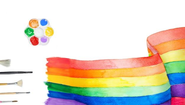 Кисть и палитра возле нарисованной радуги на белом фоне
