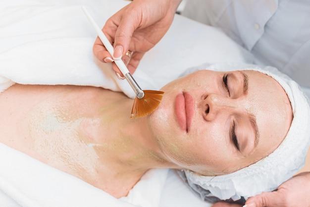 브러시는 여성의 얼굴에 효소 마스크를 적용합니다.