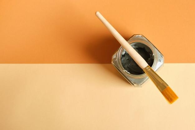 Кисть, косметическая глина в стеклянной банке на деревянной подставке, бежево-коричневый фон, копия пространства вид сверху