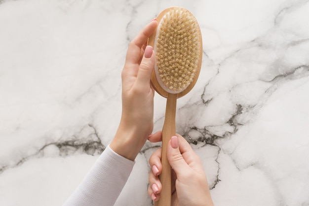 Brush for dry massage in the hands of a girl on a marble background. brush for scrubbing the body, bringing it in order, against cellulite and orange peel