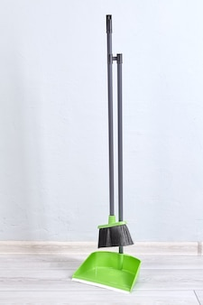 Brush and dustpan made of plastic for cleaning dust are standing indoors.