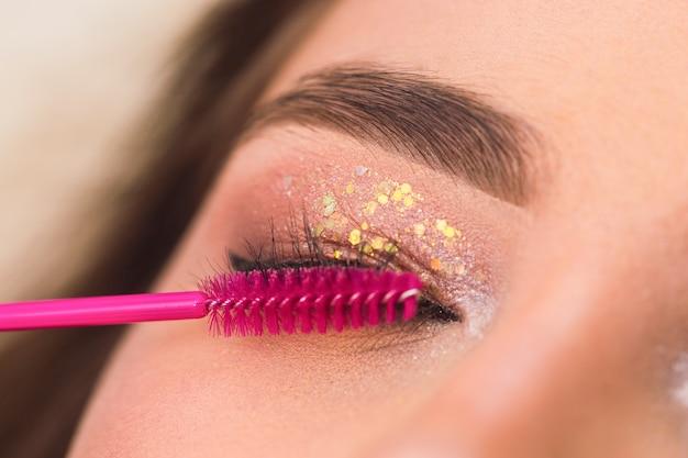 Расчешите ресницы. косметолог выщипывает брови. уход за бровями в салоне красоты. концепция макияжа и красоты