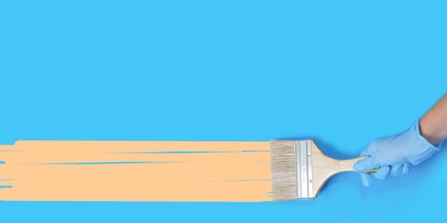 青い壁に手にペンキ用のブラシ。コピースペースのある人間の手の木製ハンドルでブラシをペイントします。