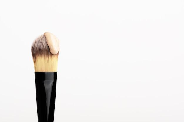 Кисть для профессионального макияжа с каплей консилера. косметический продукт для коррекции кожи лица.