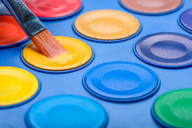 수채화 물감 클로즈업 및 수채화 물감 세트를 위한 브러시입니다. 다채로운 사진입니다. 선택적 초점, 매크로