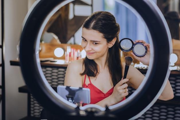 手でブラシをかけます。興奮したロマンチックなデートの準備をしながら彼女の手に化粧ブラシを保持している暗い目の女性