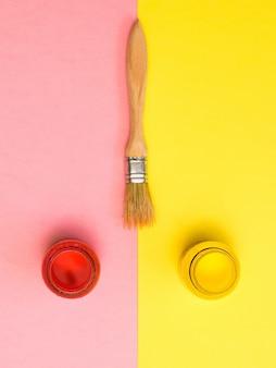 ブラシ、黄色とピンクの表面に赤と黄色のペンキの瓶