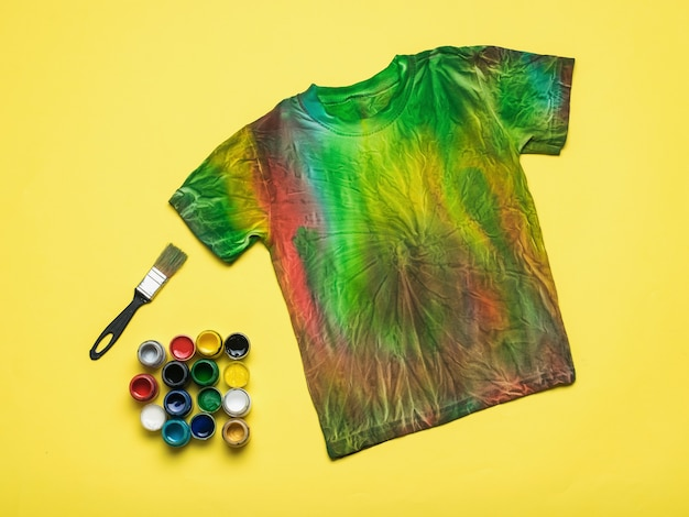 A brush, a large amount of fabric paints and a tie dye t-shirt on a yellow background. flat lay.