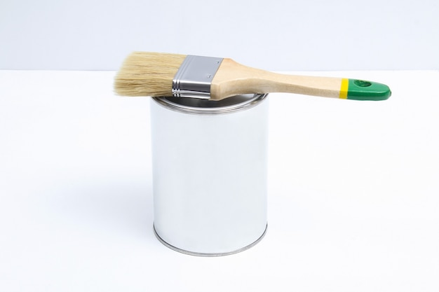 Brush lies on a can of white paint