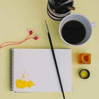 Brush on notebook near coffee and earphones