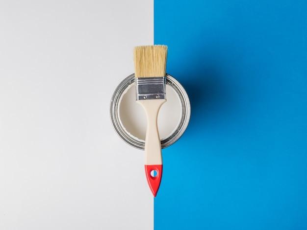 Кистью на открытой банке с белой краской по границе двух цветов. выполнение малярных работ.