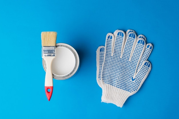 Brush on an open can of paint and gloves on a blue surface