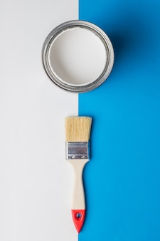 A brush and an open can of white paint on the border of white and blue colors
