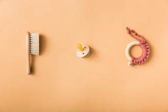 Brush; pacifier and toy on an orange background