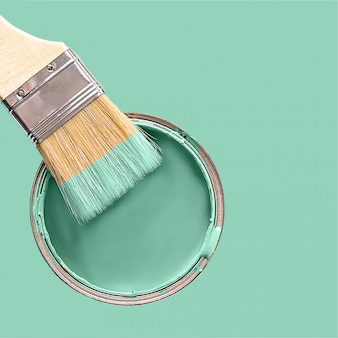 The brush in the paint color of neo mint and the can with paint color neo mint over neo mint .