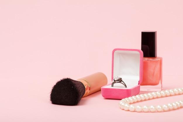 브러시, 상자에 반지, 매니큐어 및 구슬을 분홍색 배경에. 여성용 보석, 화장품 및 액세서리.
