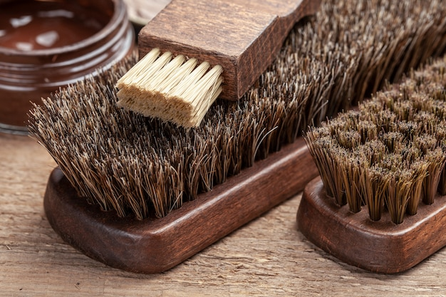 Brush for shoes. cleaning and polishing shoes with brushes. shoe polish and brush on wooden background.