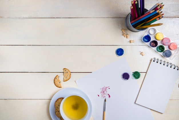 Кисть, альбом для рисования и акварельные краски на столе.