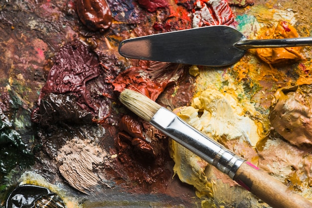 Brush and spatula on rough palette