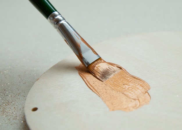 Brush stroke of gold paint with glitter on light wood