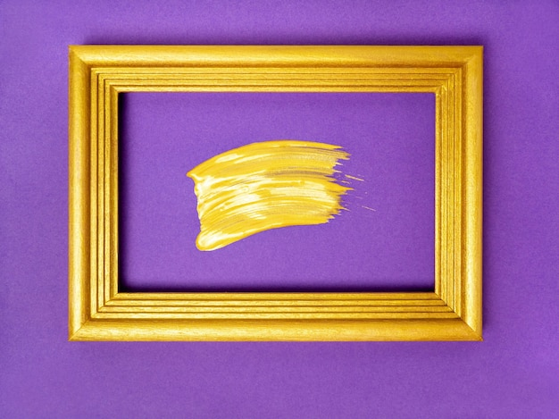 Brush stroke with gold paint in gold frame on purple paper background festive background halloween