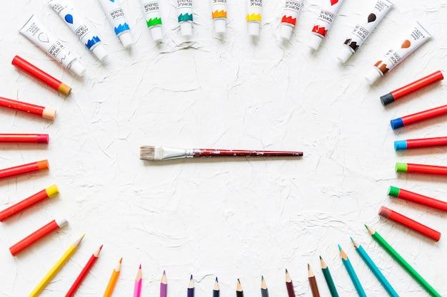 Pennello circondato da materiale pittorico