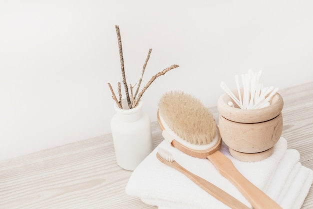 Brush; towel and cotton swabs on wooden surface